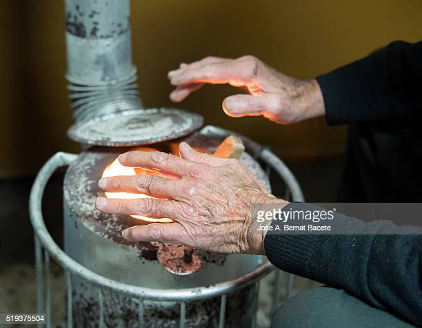 Elderly man warming up in a stove of fuelwood