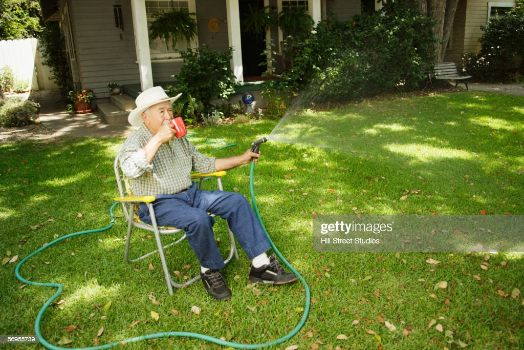 Elderly man watering lawn while sitting in chair drinking coffee : Stock Photo