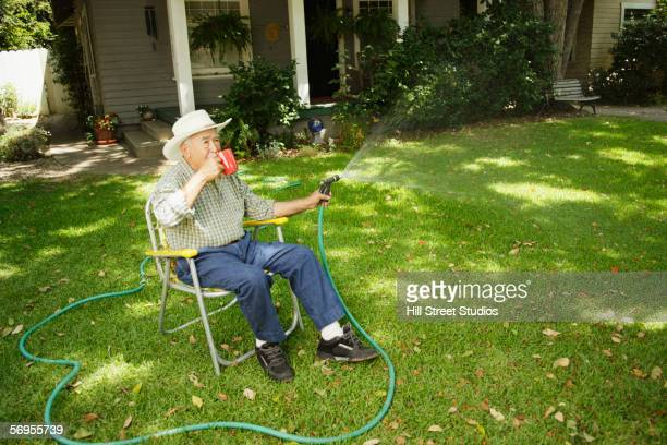 elderly man watering lawn while sitting in chair drinking coffee - outdoor chair stock pictures, royalty-free photos & images