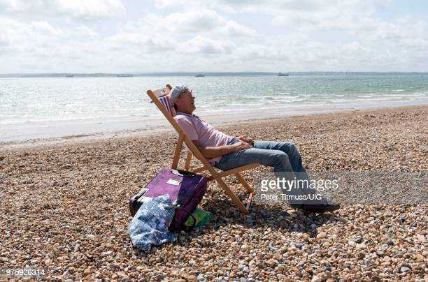Elderly man wearing a knotted handkerchief on his head relaxing on the beach