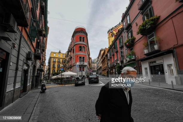 Elderly man wearing a protective mask walks in the center of the city of Naples, after a government decree declaring all of Italy a protected area to...