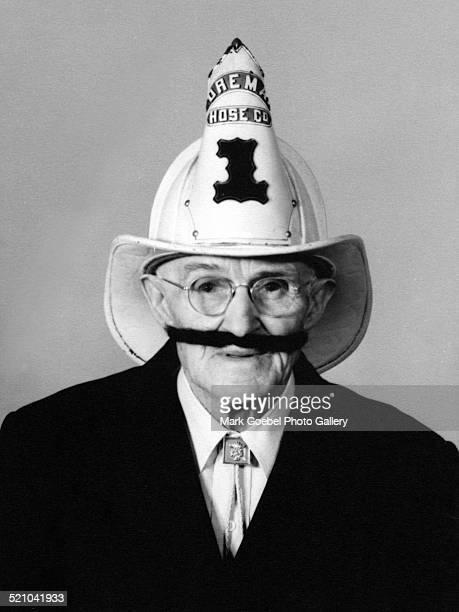 Elderly man wearing fireman hat, late 1940s.