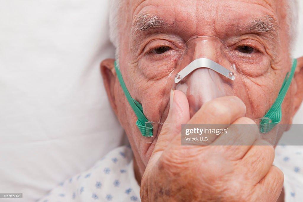 Elderly man wearing oxygen mask : Stock Photo