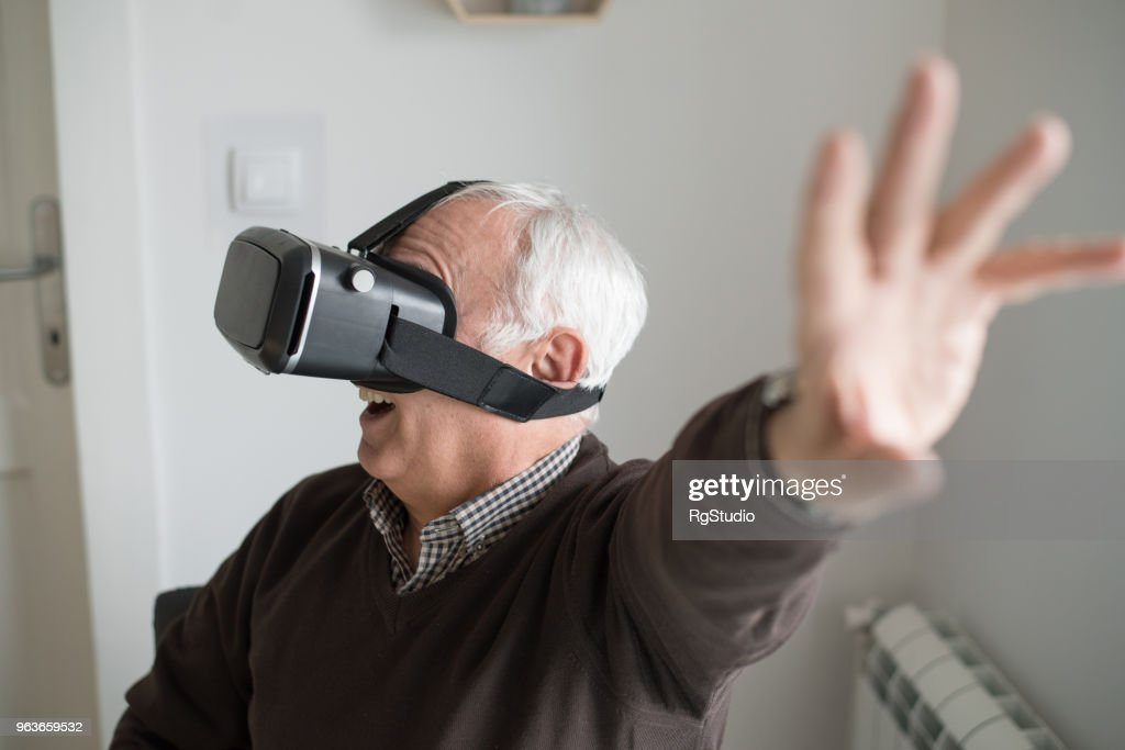 2fdd85774a2 Elderly man wearing virtual reality simulator   Stock Photo