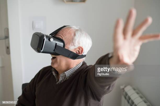 elderly man wearing virtual reality simulator - a sense of home stock photos and pictures