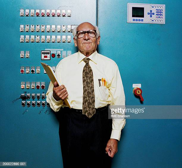 Elderly man with clipboard in front of control panel, portrait