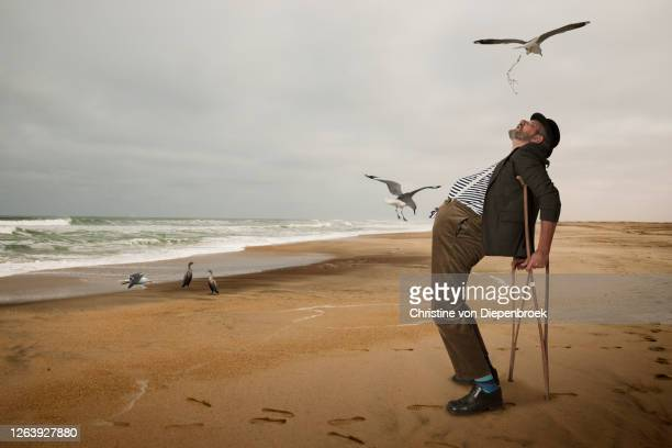 elderly man with open mouth seagull beach - bad luck stock pictures, royalty-free photos & images