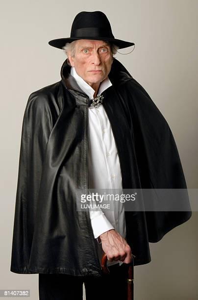 elderly man with stick wearing black cape and hat - ケープ ストックフォトと画像