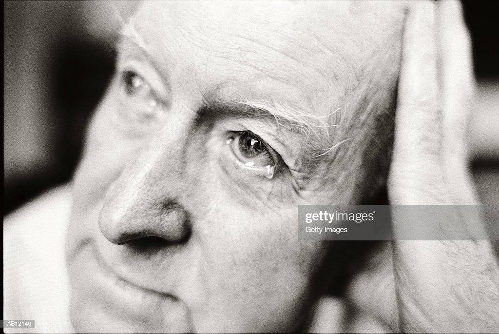 Elderly man with tear in eye, close-up (B&W) : Stock Photo