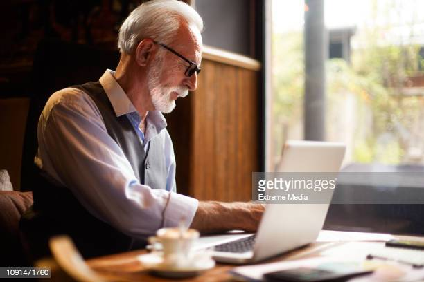 elderly manager working on his laptop in a cafeteria with a cup of coffee on the table next to him - indipendenza foto e immagini stock