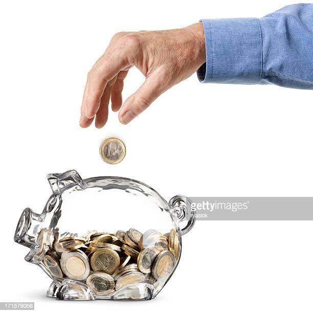 Älterer Mann Hand-Laden-Euro-Münze in Sparschwein löschen