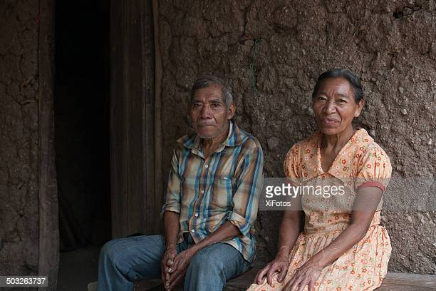 elderly mayan couple sits outside their house - honduras stock pictures, royalty-free photos & images