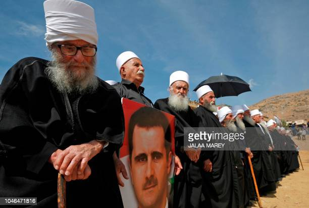 Elderly members of the Druze community stand holding a portrait of Syrian President Bashar alAssad during a rally in the Druze village of Majdal...