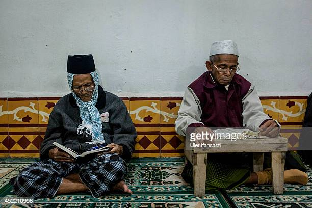 Elderly men read the Quran at a boarding school Sepuh Payaman that cares for the elderly during Ramadan on July 15 2014 in Magelang Central Java...