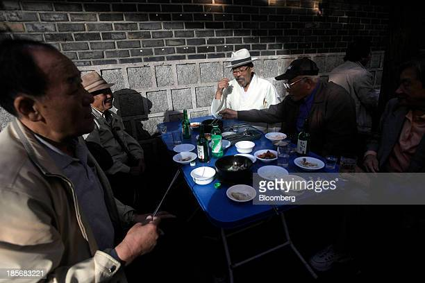 Elderly men share a meal at a street restaurant in the Jongrogu area of Seoul South Korea on Wednesday Oct 23 2013 President Park Geun Hye in her...