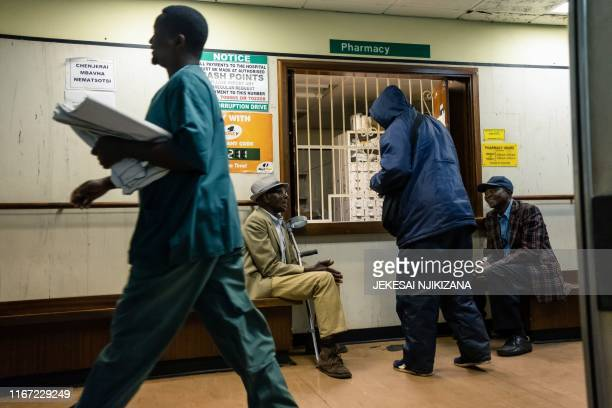 Elderly men wait for medicines at a pharmacy at Parirenyatwa hospital in Harare September 9 2019 For Zimbabwe's doctors few institutions reflect...