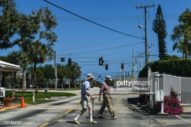 Elderly men walk inside deserted John Knox Village, a retirement community in Pompano Beach, Florida on March 21, 2020. - Almost one billion people...