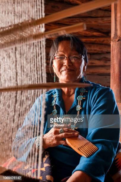 indianische navajo seniorin weben einer traditionellen stammes-decke auf einem webstuhl im inneren ein hogan - navajo kultur stock-fotos und bilder