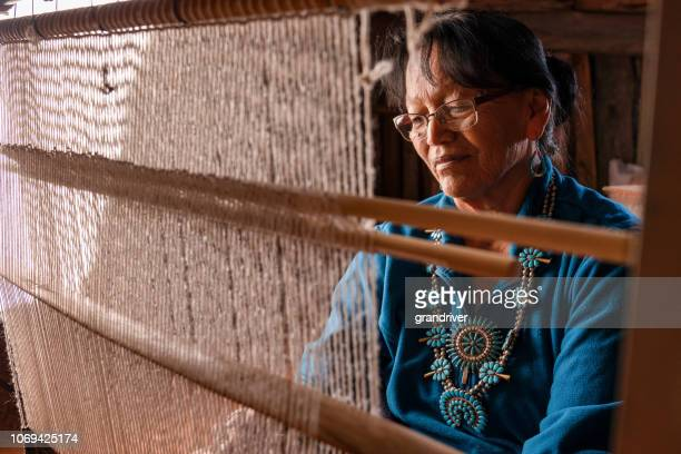 elderly native american navajo woman weaving a traditional tribal blanket on a loom inside a hogan - native american reservation stock pictures, royalty-free photos & images