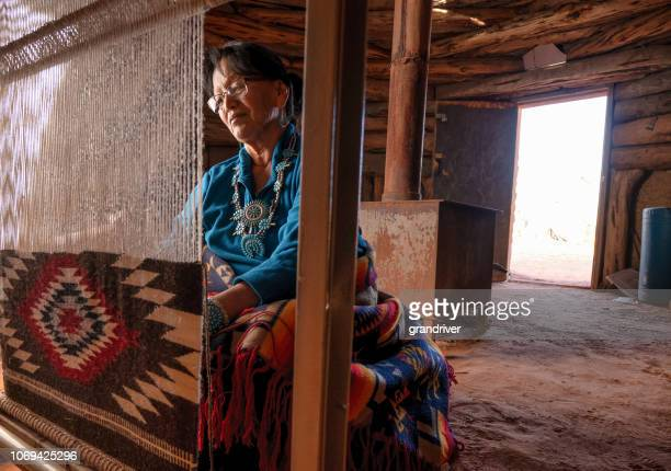 elderly native american navajo woman weaving a traditional tribal blanket on a loom inside a hogan - southwest usa stock pictures, royalty-free photos & images