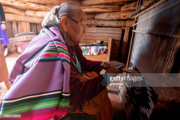 elderly native american navajo woman weaving a traditional tribal blanket on a loom inside a hogan - navajo hogan stock photos and pictures