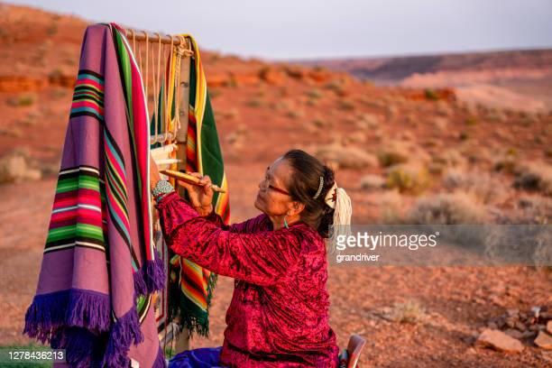 アリゾナ州北部のモニュメントバレー部族公園近くの夕暮れ時の砂漠の本物のネイティブアメリカン織機に伝統的な毛布や敷物を織る高齢のナバホ女性 - ナバホ文化 ストックフォトと画像