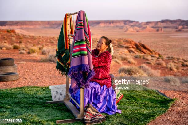 elderly navajo woman weaving a traditional blanket or rug on an authentic native american loom in the desert at dusk near the monument valley tribal park in northern arizona - cherokee indian women stock pictures, royalty-free photos & images