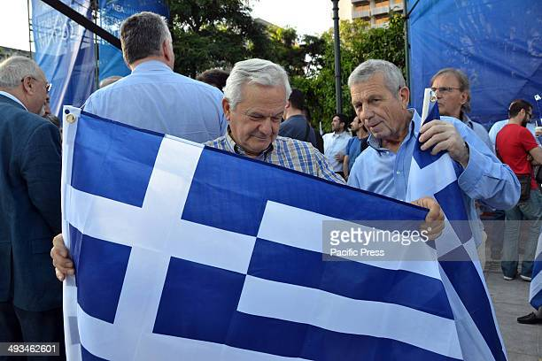 Elderly New Democracy supporters proudly hold a Greek flag in their hands Prime Minister Antonis Samaras delivered his message with the New Democracy...