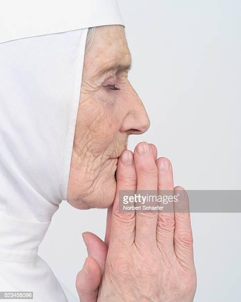 Elderly Nun Praying