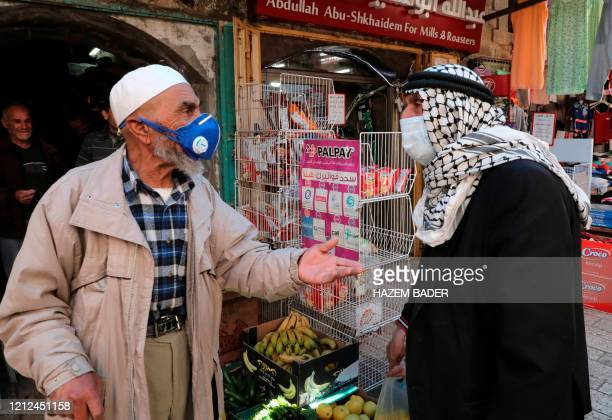 Elderly Palestinian men wearing protective face masks engage in a conversation in the centre of the West Bank city of Hebron during the novel...