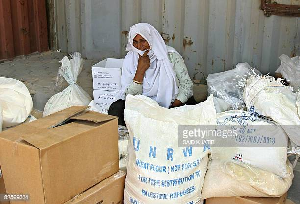 A elderly Palestinian refugee sits amidst flour sacs and boxes donated by the United Nations Relief and Works Agency for Palestine Refugees on July...