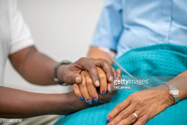 elderly patient is comforted by medical personnel stock photo - ethnicity stock pictures, royalty-free photos & images