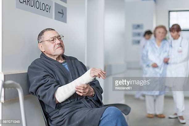 Elderly patient with arm bandage waiting in hospital