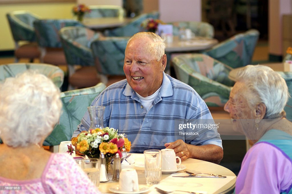 Elderly People At Dining Room Table In Nursing Home Stock