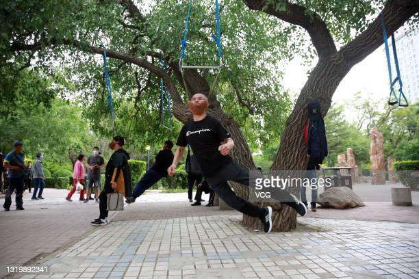 Elderly people exercise with cervical traction devices attached to a tree at a park on May 24, 2021 in Shenyang, Liaoning Province of China.