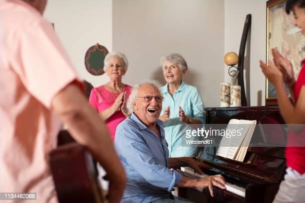 elderly people making music in retirement home - altersheim stock-fotos und bilder
