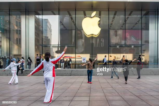 Elderly people perform square dance in front of an Apple store on Nanjing East Road on November 3 2017 in Shanghai China iPhone X go on sale on...