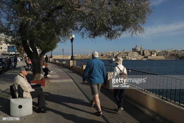 Elderly people relax along the Tigne Seafront promenade as Valletta including the dome of the Basilica of Our Lady of Mount Carmel stands behind on...
