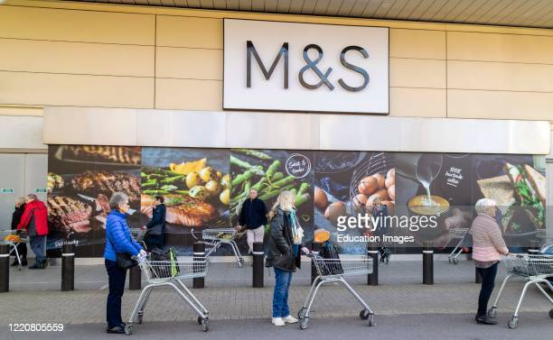 Elderly people standing in line and six feet apart wait to enter a supermarket for the 'silver hour' shopping experience. During the Coronavirus...