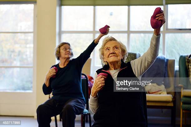 Elderly people take part in an exercise class at the AgeUK Ann Owens Centre on December 4 2013 in Barnet England AgeUK are a nationwide charity...