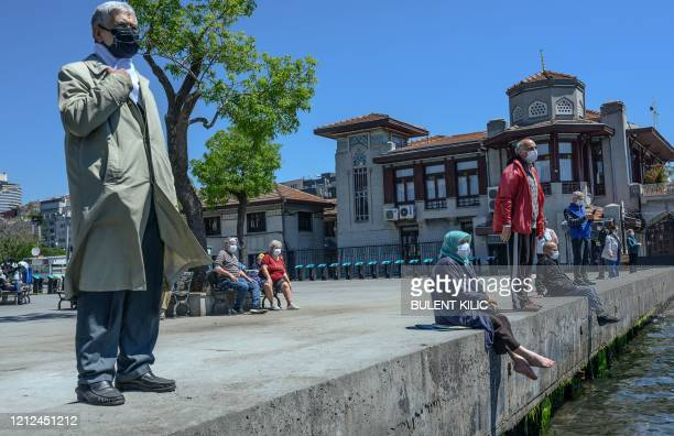 TOPSHOT Elderly people wearing a protective face mask sit and look at the Bosphorus on May 10 at Besiktas Istanbul after a month and a half of...