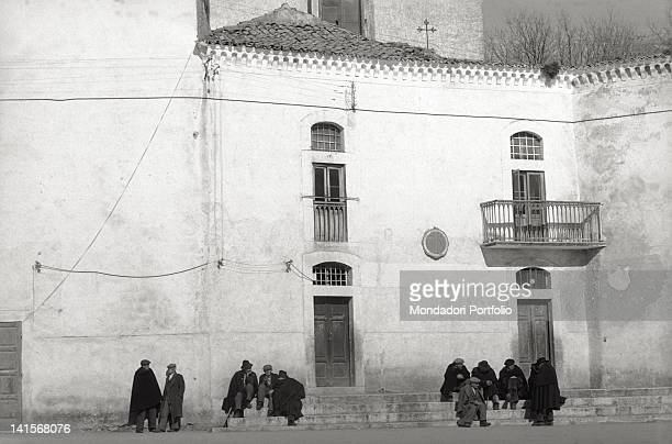 Elderly people wearing cloaks seated on the steps of a church at San Giovanni Rotondo Italy