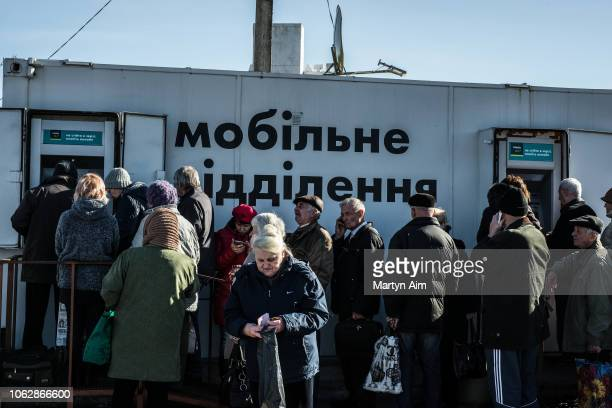 Elderly people who have crossed a checkpoint from LNR into Ukrainian government controlled territory withdraw money from mobile ATM bank machines on...