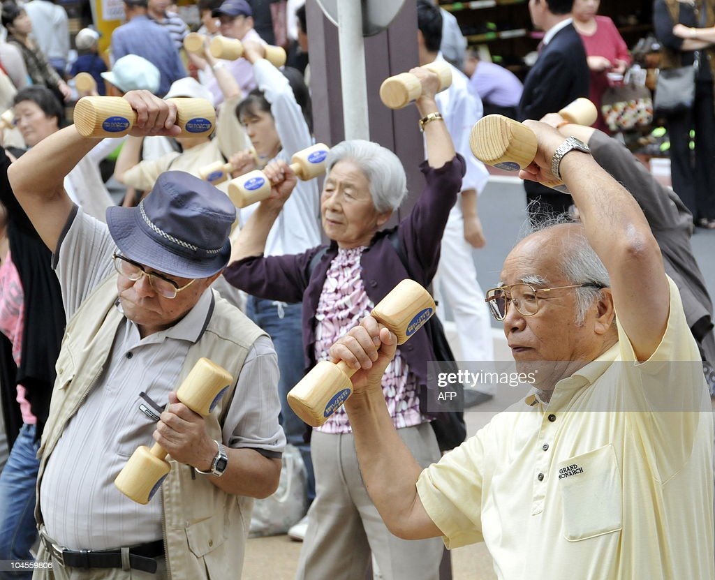 Elderly people work out with wooden dumb : News Photo
