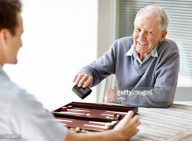 elderly person playing backgammon with a young guy - backgammon stock pictures, royalty-free photos & images