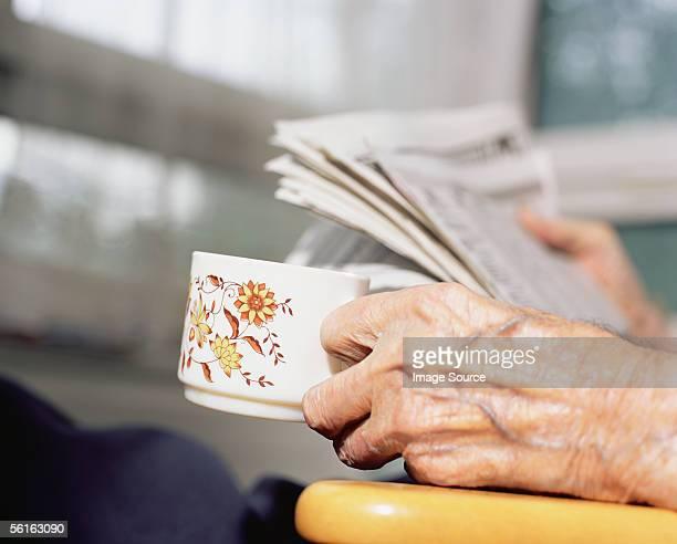 Elderly person reading the newspaper