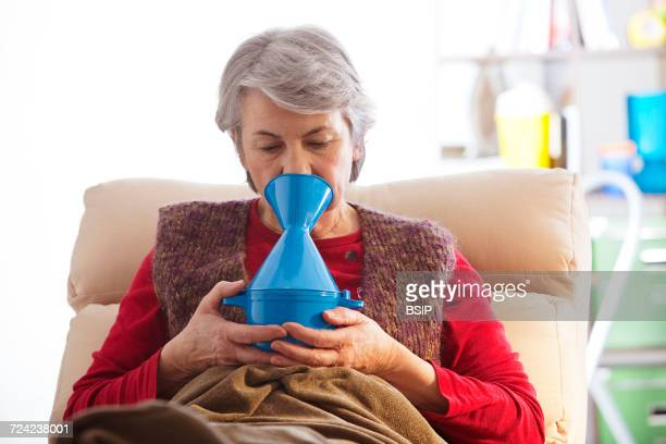 Elderly person taking inhalation