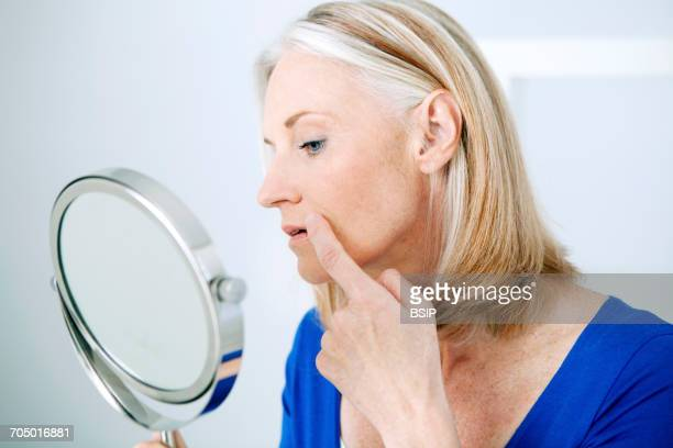 elderly person with mirror - herpes foto e immagini stock