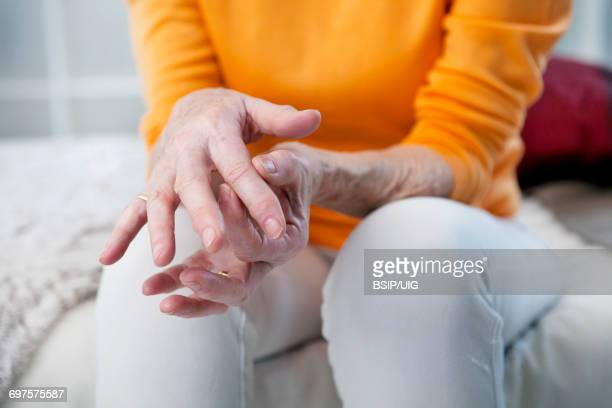 elderly person with painful hand   - rheumatism stock pictures, royalty-free photos & images