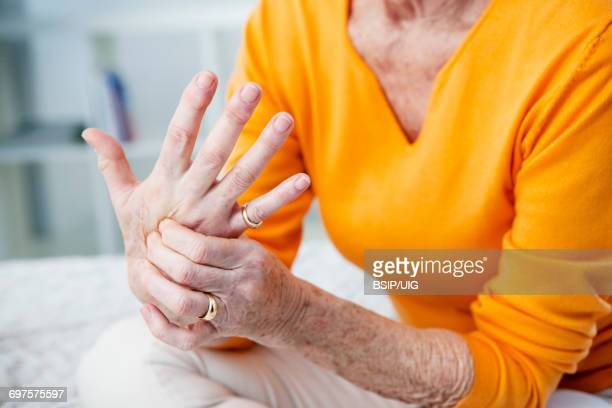 elderly person with painful hand   - osteoarthritis stock photos and pictures